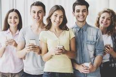 Gruppe junge positive Freunde, die Telefone halten Stockbild