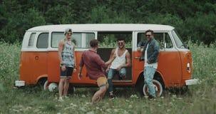Gruppe junge stilvolle Kerle haben die schöne Zeit zusammen am Picknick, am Tanzen und am Kühlen vor einem Retro- Bus stock footage
