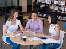 Gruppe junge Studenten an der Bibliothek Lizenzfreie Stockfotos