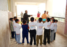 Gruppe Jungen in den Kreisen, die Anweisungen vom Lehrer erhalten Stockfoto