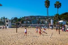 Gruppe Jungen, die Flugball auf dem Strand spielen lizenzfreies stockfoto