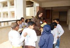Gruppe Jungen in einem Kreis, der Ausweise vom weiblichen Lehrer erhält Lizenzfreie Stockfotografie