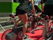 Gruppe Jungen und Mädchen an der Turnhalle: Training mit spinnenden Fahrrädern Stockfoto