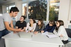 Gruppe junger Mann und weibliche Jugendlichhochschulstudenten in der Schule, die auf Klassenzimmer lernend und an Projekt togethe stockbilder