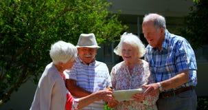 Gruppe kaukasische ältere Paare besprechend über digitaler Tablette im Garten des Pflegeheims 4k stock video