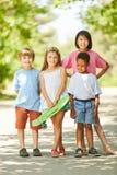 Gruppe Kinder als Freunde mit einem Skateboard lizenzfreies stockfoto