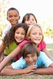 Gruppe Kinder angehäuft oben im Park Stockfotografie