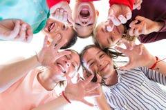 Gruppe Kinder des verschiedenen Alters, das im Kreis, untersuchend unten Kamera steht stockfotografie