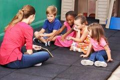 Gruppe Kinder, die über Buch in der Vorschule sprechen Lizenzfreie Stockfotos