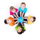 Gruppe Kinder, die auf dem Boden in einem Kreis sitzen. Stockbilder