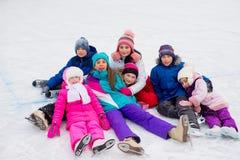 Gruppe Kinder, die auf dem Eis sitzen lizenzfreies stockfoto