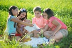 Gruppe Kinder, die auf Gras spielen Stockfotos