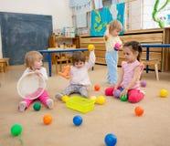 Gruppe Kinder, die Bälle in der Kindergarten- oder Kindertagesstättenmitte spielen lizenzfreie stockbilder
