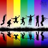 Gruppe Kinder, die über einen colore Hintergrund springen Stockfotografie