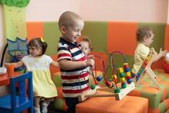 Gruppe Kinder, die in der Kindergarten- oder Kindertagesstättenmitte spielen Stockfotos