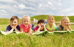 Gruppe Kinder, die draußen auf Decke oder Abdeckung liegen Stockbild