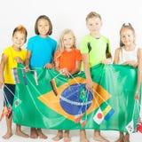 Gruppe Kinder, die eine Brasilien-Flagge halten Stockfotografie