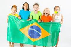 Gruppe Kinder, die eine Brasilien-Flagge halten Lizenzfreies Stockfoto
