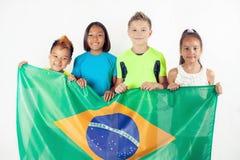 Gruppe Kinder, die eine Brasilien-Flagge halten Stockbilder