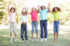 Gruppe Kinder, die in einer Luft im Park springen Stockbild