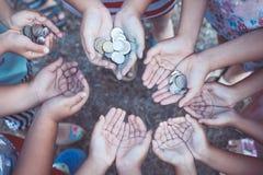 Gruppe Kinder, die Geld in den Händen im Kreis zusammenhalten Lizenzfreie Stockfotos