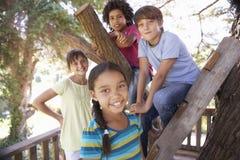 Gruppe Kinder, die heraus zusammen im Baumhaus hängen stockfotos