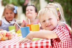 Gruppe Kinder, die im Freientee-Party genießen Stockbilder