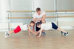 Gruppe Kinder, die Kindergymnastik in der Turnhalle mit Kindergärtnerin tun Lizenzfreies Stockfoto