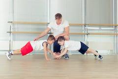 Gruppe Kinder, die Kindergymnastik in der Turnhalle mit Kindergärtnerin tun Lizenzfreie Stockfotos