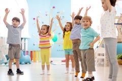 Gruppe Kinder, die Kindergymnastik im Kindergarten tun stockfotografie