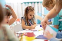 Gruppe Kinder, die mit Bleistiften im Kindergarten zeichnen stockfoto