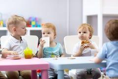 Gruppe Kinder, die Nahrung in der Kindertagesstättenmitte essen lizenzfreies stockbild