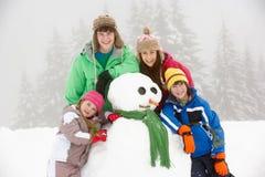 Gruppe Kinder, die Schneemann am Ski-Feiertag aufbauen Stockbilder