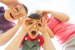 Gruppe Kinder, die Spaß haben und draußen Gesichter machen stockfotografie
