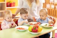 Gruppe Kinder, die von den Platten in der Tagesstätte essen stockfotos