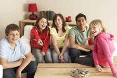 Gruppe Kinder, die zu Hause Fernsehen stockbild