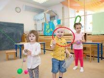 Gruppe Kinder, die zusammen in der Kindergarten- oder Kindertagesstättenmitte spielen stockfoto