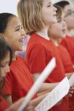 Gruppe Kinder, die zusammen im Chor singen Stockbild