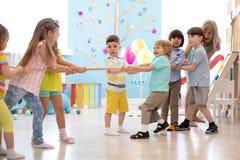 Gruppe Kinder in einem Seil-ziehenden Wettbewerb im Kindergarten stockbild