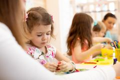 Gruppe Kinder mit dem Lehrer in einem Kindergarten Kinder schaffen Handwerk aus farbigem Papier heraus lizenzfreies stockfoto
