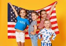Gruppe Kinder mit Flagge von den Vereinigten Staaten von Amerika USA auf gelbem Hintergrund lizenzfreie stockbilder