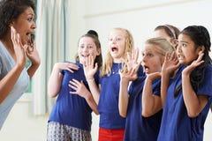 Gruppe Kinder mit Lehrer Enjoying Drama Class zusammen lizenzfreie stockbilder