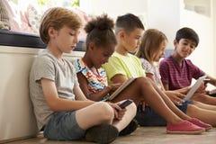 Gruppe Kinder-Sit On Floor And Use-Technologie lizenzfreie stockbilder