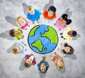 Gruppe Kinder um Kugel in Grey Background Stockbilder