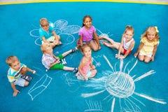 Gruppe Kinder zeichnen mit Kreide auf Spielplatz Stockbild