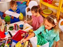 Gruppe Kinder zeichnet Bilder im kleinen Kindergarten Stockfotografie
