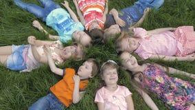 Gruppe Kindergartenkinder, die auf dem Gras am Park und mit dem Lächeln sich entspannen liegen stock footage