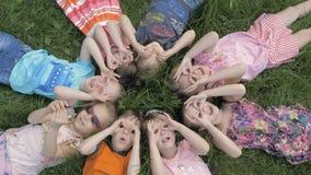 Gruppe Kindergartenkinder, die auf dem Gras am Park und mit dem L?cheln sich entspannen liegen stock video