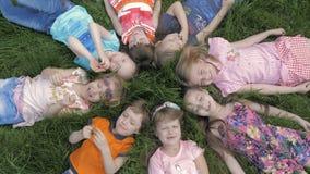 Gruppe Kindergartenkinder, die auf dem Gras am Park und mit dem L?cheln sich entspannen liegen stock video footage