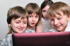 Gruppe Kindfreunde, die Computerspiele spielen Lizenzfreie Stockfotos